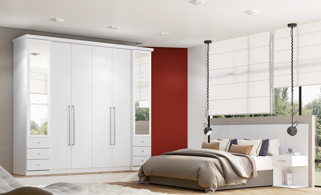 Ambiente de quarto com guarda-roupa branco e cama.